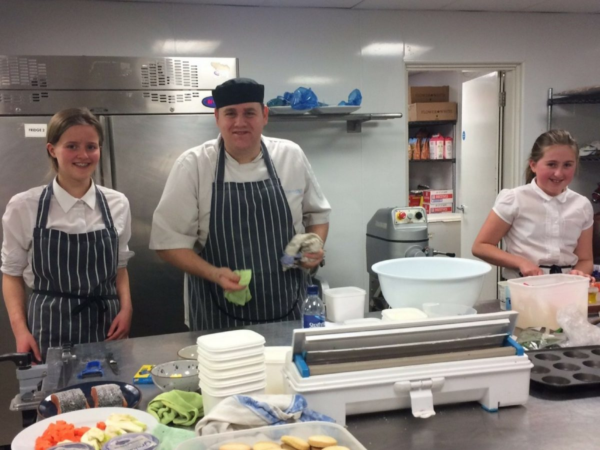 Two high school students preparing for a cookery competition